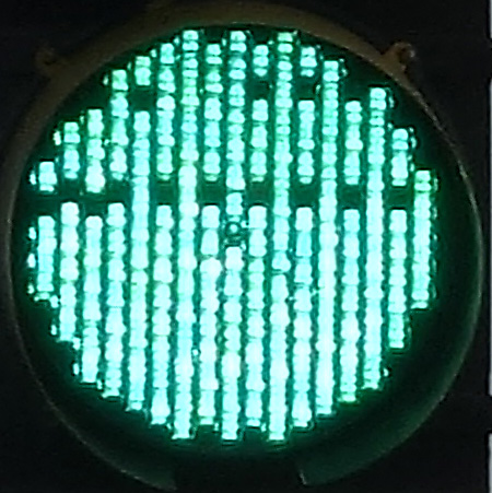 a green signal light wth some dark pixels in alternating columns; location: Elm Street near Davis Square, Somerville, MA