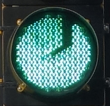 green traffic light with a J-shaped dark scar; location: Highland Ave, Somerville MA