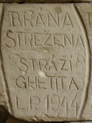 Inscription: Brána strežena stráží ghetta