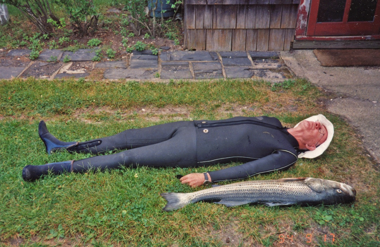 Dennis Flanagan in a wet suit, lying on the lawn next to the striped bass he just speared in Great South Bay.