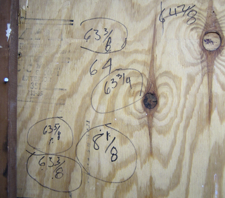 plywood panel with seven measurements in crayon or magic marker